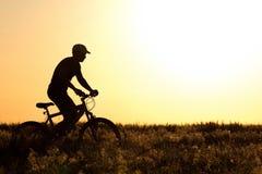 Sylwetka mężczyzna jedzie bicykl w polu Obrazy Royalty Free