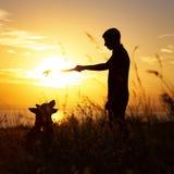Sylwetka mężczyzna odprowadzenie z psem na polu przy zmierzchem, chłopiec bawić się z zwierzęciem domowym outdoors, pojęciem szcz zdjęcie royalty free