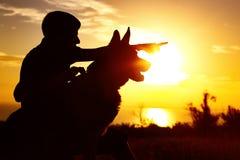 Sylwetka mężczyzna odprowadzenie z psem na polu przy zmierzchem, faceta szkolenia zwierzę domowe w lato naturze, chłopiec daje ro zdjęcie stock