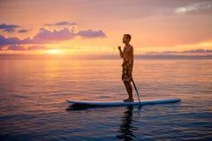 Sylwetka mężczyzna Paddleboarding Przy zmierzchem Zdjęcie Stock