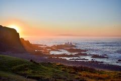 Sylwetka mężczyzna połów podczas gdy siedzący na nabrzeżnych skałach obrazy stock