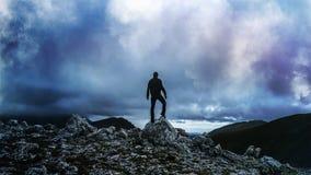 Sylwetka mężczyzna pozycja Na Skalistej góry wierzchołka szczycie Patrzeje Buntowniczo Przy Zniechęcającą burzą zdjęcie stock