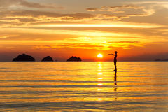 Sylwetka mężczyzna pozycja w morzu przy zmierzch wysp tłem na tropikalnej wyspie Obrazy Royalty Free