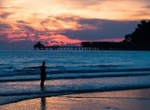 Sylwetka mężczyzna pozycja w oceanie przy zmierzchem Fotografia Royalty Free