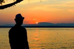 Sylwetka mężczyzna przy pięknym zmierzchem na plaży Tło Młody człowiek patrzeje zmierzch obraz royalty free