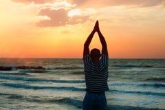 Sylwetka mężczyzna robi joga przy zmierzchem Obraz Stock