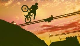 Sylwetka mężczyzna robi skokowi z bmx rowerem Zdjęcia Royalty Free