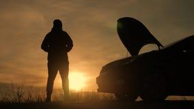 Sylwetka mężczyzna stoi obok psującego się samochodu podczas gdy zmierzch zdjęcie wideo