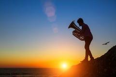 Sylwetka mężczyzna sztuki Tuba na dennym brzeg przy zadziwiającym zmierzchem relaksuje Fotografia Stock