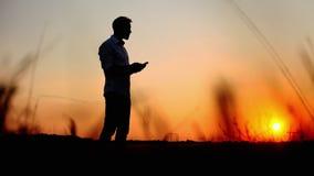 Sylwetka mężczyzna używa telefon komórkowego przeciw słońcu w wieczór czasie na zmierzchu zbiory