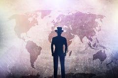 Sylwetka mężczyzna w kapeluszowej pozyci przed światową mapą na grunge betonowej ścianie fotografia royalty free
