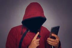 Sylwetka mężczyzna w kapiszonie na czarnym tle, jego twarz no jest widoczna hacker trzyma telefon w jego rękach Co obraz royalty free
