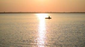 Sylwetka mężczyzna wioślarstwo w małej gumowej łodzi przy świtem zbiory