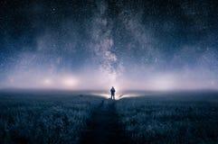 Sylwetka mężczyzna z pochodnią w polu, patrzeje światła na horyzoncie na markotnej mglistej nocy Z galaxy gwiazdy ove zdjęcia stock