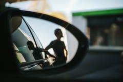 Sylwetka mężczyzna zobaczy podczas bocznego widoku lustra podczas gdy refueling przy benzynową stacją fotografia royalty free
