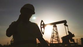 Sylwetka m??czyzny in?ynier nadzoruje miejsce ropy naftowej produkcja przy zmierzchem z telefonem zbiory
