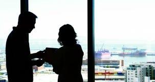 Sylwetka męscy i żeńscy kierownictwa dyskutuje nad cyfrową pastylką