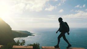 Sylwetka Męski wycieczkowicz z plecaka odprowadzeniem na krawędzi drogi w wyspach kanaryjskich wysokich nad ocean zbiory