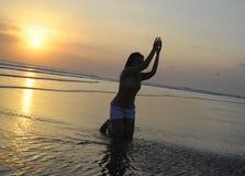 Sylwetka młoda Azjatycka kobieta bawić się z piaskiem, wodą na morzu przy zmierzch plażą i Obraz Royalty Free
