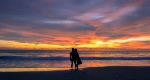 Sylwetka młoda Azjatycka pary pozycja na plaży gdy zmierzch zdjęcie stock