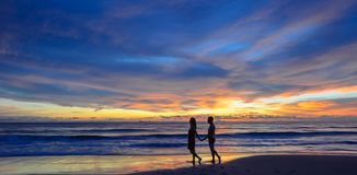 Sylwetka młoda Azjatycka pary pozycja na plaży gdy zmierzch zdjęcia royalty free