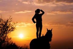 Sylwetka młoda dziewczyna która stoi na koniu i patrzeje w odległość Obraz Royalty Free
