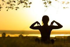 Sylwetka młoda kobieta angażował w sprawności fizycznej w naturze przy zmierzchem, sport kobiety profilem pojęciem sport i healhc Fotografia Stock