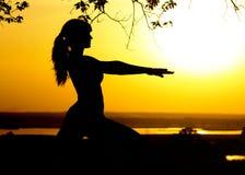 Sylwetka młoda kobieta angażował w sprawności fizycznej w naturze przy zmierzchem, sport kobiety profilem pojęciem sport i healhc Zdjęcie Royalty Free