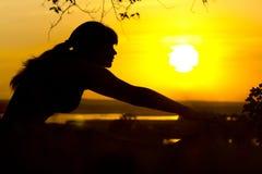 Sylwetka młoda kobieta angażował w sprawności fizycznej w naturze przy zmierzchem, sport kobiety profilem pojęciem sport i healhc Fotografia Royalty Free