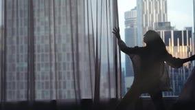 Sylwetka młoda kobieta biega zasłony na dużych nadokiennych wzrost rękach out i otwiera i przyglądający jej mieszkanie na zbiory wideo