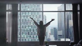 Sylwetka młoda kobieta biega zasłony na dużym okno out i otwiera i przyglądający jej mieszkanie na miasto budynkach zbiory