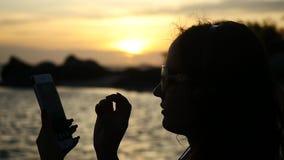 Sylwetka młoda kobieta używa telefon komórkowy pod sunse swobodny ruch 1920x1080 zbiory