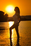 Sylwetka młoda piękna kobieta w rzece nad zmierzchu niebem Żeński perfect ciało kontur przy plażą w mrocznej scenerii Obrazy Stock