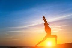 Sylwetka młoda sprawności fizycznej kobieta robi ćwiczeniom na morze plaży podczas zmierzchu Zdjęcia Stock
