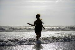 Sylwetka młoda szczęśliwa Azjatycka kobieta relaksował patrzeć dzikie denne fala na zmierzch tropikalnej plaży Zdjęcie Stock