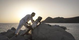 Sylwetka młoda szczęśliwa para ma zabawę na plaży kołysa przy wschodem słońca Zdjęcie Royalty Free