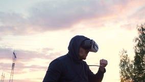 Sylwetka młodego człowieka bokser w VR 360 słuchawki szkoleniu dla kopać w rzeczywistości wirtualnej walce na zmierzchu przy mias zbiory