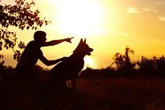 Sylwetka młodego człowieka odprowadzenie z psem na polu przy zmierzchem, chłopiec z jego zwierzęciem domowym cieszy się naturę, p zdjęcia royalty free