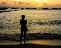 Sylwetka młodej kobiety dopatrywania morza zmierzch Dramata pojęcie Obrazy Royalty Free