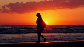 Sylwetka młodej kobiety odprowadzenie wzdłuż dennej plaży na zmierzchu tle zbiory wideo