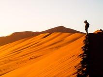 Sylwetka młody człowiek pozycja na czerwonej wydmowej grani w Sossusvlei, Namib pustynia, Namibia, Afryka Zdjęcie Stock