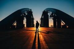 Sylwetka młody człowiek pozycja przy mostem Fotografia Stock