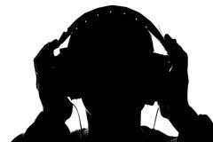 Sylwetka młody człowiek słucha muzyka z hełmofonami fotografia stock