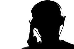 Sylwetka młody człowiek słucha muzyka z hełmofonami Zdjęcie Royalty Free