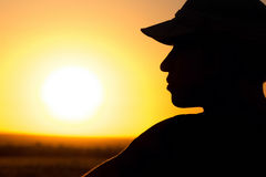 Sylwetka młody człowiek w polu przy zmierzchem Zdjęcia Royalty Free