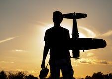Sylwetka młody człowiek z wzorcowym rc samolotem Zdjęcia Royalty Free