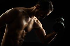 Sylwetka młody mięśniowy sprawność fizyczna mężczyzna na czerni Zdjęcia Royalty Free