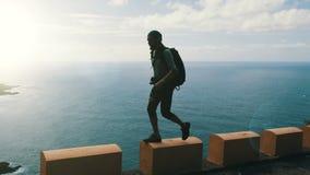 Sylwetka młody ufny brodaty wycieczkowicz z plecaka odprowadzeniem na krawędzi drogi na wyspach kanaryjskich wysokich nad zdjęcie wideo