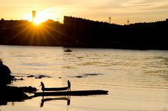 Sylwetka młodzi człowiecy niesie czółno zdala od jeziora w zmierzchu Obraz Royalty Free