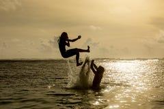Sylwetka młodej kobiety doskakiwanie z oceanu Obrazy Royalty Free